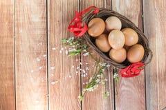 Pâques - Hen Eggs dans un panier en osier avec un ruban et un ressort la Floride Photographie stock libre de droits