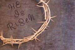 Pâques il est citation levée entouré par une couronne des épines sur un te Images stock
