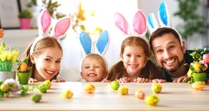 Pâques le père et les enfants heureux de mère de famille se préparent à la maison de vacances avec des oeufs images libres de droits