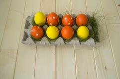 Pâques Les oeufs de pâques sont jaunes et oranges Mensonge d'oeufs dans le récipient pour des oeufs Herbe verte Photographie stock libre de droits