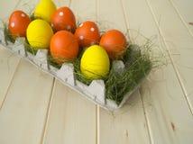 Pâques Les oeufs de pâques sont jaunes et oranges Mensonge d'oeufs dans le récipient pour des oeufs Herbe verte Photographie stock