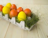 Pâques Les oeufs de pâques sont jaunes et oranges Mensonge d'oeufs dans le récipient pour des oeufs Herbe verte Images stock