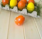 Pâques Les oeufs de pâques sont jaunes et oranges Mensonge d'oeufs dans le récipient pour des oeufs Herbe verte Photos libres de droits
