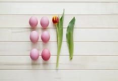 Pâques Les oeufs et les tulipes de pâques roses se trouvent sur un fond en bois Configuration plate Photographie stock libre de droits