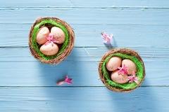 Pâques niche avec des oeufs et fleurit la décoration sur le fond bleu Images libres de droits