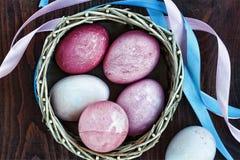 Pâques Oeufs de pâques dans un panier, rubans colorés, vue supérieure Photo libre de droits