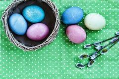 Pâques Oeufs de pâques dans un panier sur un fond vert et des rubans colorés Joyeuses Pâques Photos stock