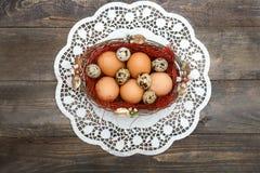 Pâques, oeufs de pâques dans un panier sur un fond en bois Image libre de droits