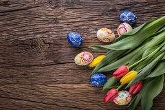 Pâques Oeufs de pâques et tulipes fabriqués à la main de ressort sur la vieille table en bois Image libre de droits
