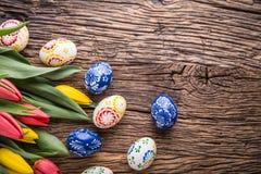 Pâques Oeufs de pâques et tulipes fabriqués à la main de ressort sur la vieille table en bois Images stock