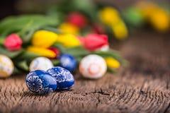 Pâques Oeufs de pâques et tulipes fabriqués à la main de ressort sur la vieille table en bois Photographie stock libre de droits