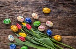 Pâques Oeufs de pâques et tulipes fabriqués à la main de ressort sur la vieille table en bois Photographie stock