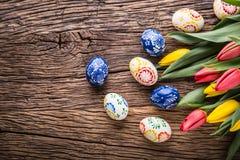 Pâques Oeufs de pâques et tulipes fabriqués à la main de ressort sur la vieille table en bois Photos libres de droits