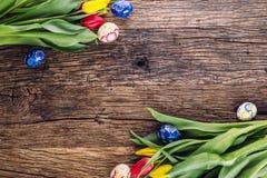 Pâques Oeufs de pâques et tulipes fabriqués à la main de ressort sur la vieille table en bois Photo libre de droits
