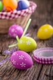 Pâques Oeufs de pâques multicolores dans un panier sur une table en bois Photo stock