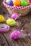 Pâques Oeufs de pâques multicolores dans un panier sur une table en bois Photos stock