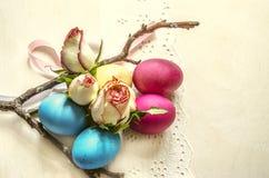 Pâques a peint des oeufs avec les bourgeons roses à une frontière blanche de dentelle avec une branche sèche Photos stock