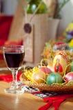 Pâques a peint les oeufs et la glace de vin sur la table Image stock
