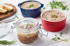 Pâté de canard différent dans des pots avec du pain frais et des herbes Image stock