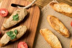 Pâté de foie sur le pain sur le plateau en bois Photographie stock libre de droits