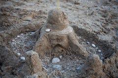 Pâté de sable entouré par des roches sur la plage Bâtiment fait de sable Divertissement d'enfants faisant des pâtés de sable Temp photographie stock libre de droits