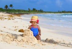 Pâté de sable mignon de bâtiment de petite fille sur la plage Photographie stock