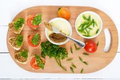 Pâté sensible de foie de poulet dans des cuvettes en céramique Canape sur la planche à découper Photos libres de droits