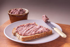 Pâté on toast. Liver pâté on toast on plate with knife and small bowl Stock Photography