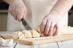 Pâte à levure douce crue sur une plaque de cuisson, raisin sec remplissant de petits pains RP Photos stock