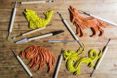 Pâte à modeler d'argile de figurine dans un atelier avec des outils sur un Ba en bois Image stock