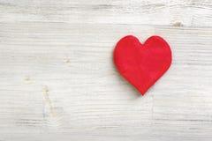 Pâte à modeler peu de coeur rouge s'étendant sur une surface en bois légère Photo stock