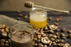 Pâte d'écrou des arachides, des noix et des noisettes avec du miel photos stock