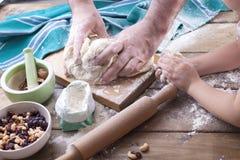 Pâte dans les mains d'un homme et de la main d'une petite fille sur un conseil en bois et d'un fond de bois, d'une serviette vert photo libre de droits