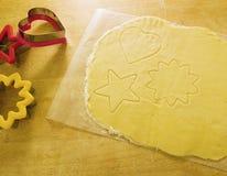 Pâte de biscuit avec des coupeurs de biscuit Photographie stock libre de droits