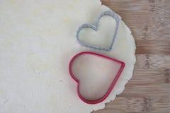 Pâte de biscuit de sucre avec les coupeurs en forme de coeur Images stock