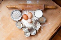 Pâte de cuisson sur le vieux conseil en bois, avec de rétros coupeurs de goupille et de biscuit de vintage Photographie stock libre de droits