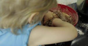 Pâte de mélange de chocolat d'enfant, fille faisant le gâteau dans la cuisine banque de vidéos
