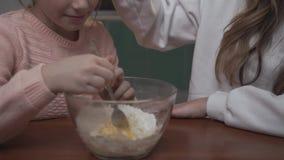 Pâte de mélange de petite fille se reposant à la table dans la cuisine avec sa soeur plus âgée Une fille plus âgée félicite sa so banque de vidéos