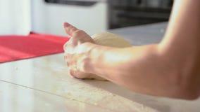 Pâte de malaxage de Baker en farine sur la table Fermez-vous des mains femelles fonctionnant avec la pâte banque de vidéos