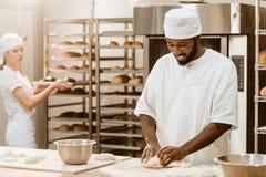 pâte de malaxage de boulanger beau d'afro-américain tandis que son collègue féminin travaillant au fond image libre de droits