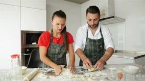 Pâte de malaxage de couples drôles et amusement de avoir avec de la farine sur la cuisine banque de vidéos