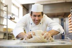 Pâte de malaxage de Baker dans la boulangerie Photos stock