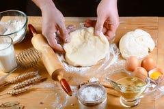 Pâte de roulement de Baker avec des ingrédients de recette de pain, de pizza ou de tarte de farine avec les mains, nourriture sur photos libres de droits