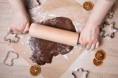 Pâte de roulement, bonhommes en pain d'épice de cuisson, faisant le gingerbr de Noël photos libres de droits