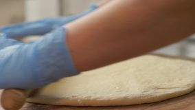 Pâte de roulement de fabricant de pizza de main sur la table pour faire dans cuire au four la fin de restaurant  banque de vidéos