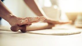 Pâte de roulement de femme sur la table en bois avec la goupille en bois image stock