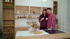 Pâte de roulement de fille d'enfant en bas âge tandis que ses parents heureux buvant du café dans la cuisine banque de vidéos