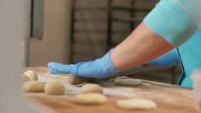 Pâte de roulement de main de Baker avant de faire des pâtisseries cuire au four sur la table dans la fin de boulangerie  clips vidéos