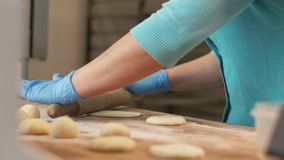 Pâte de roulement de main de Baker avant de faire des pâtisseries cuire au four sur la table dans la fin de boulangerie  image stock