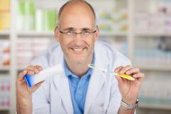 Pâte dentifrice masculine de Holding Toothbrush And de pharmacien dans la pharmacie photo libre de droits